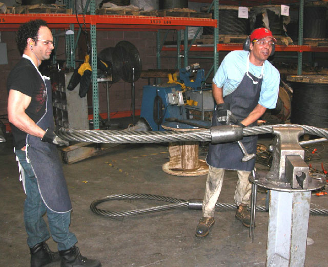 Two workers manufacturing a lifting sling